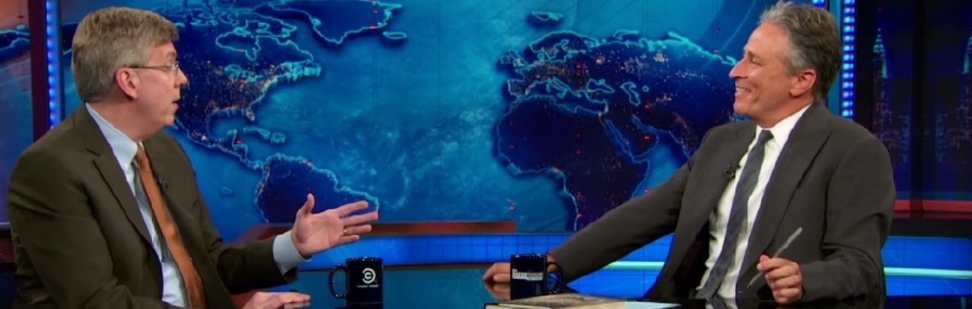 Bill Dedman talks with Jon Stewart on the Daily Show set