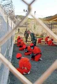 Detainees in orange kneeling at Guantanamo prison