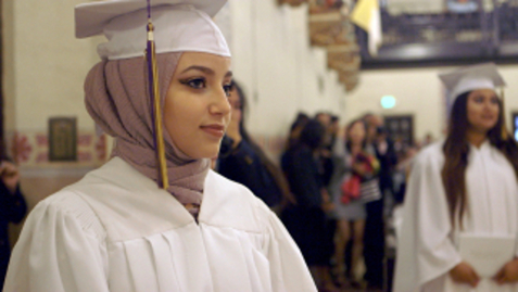 Muslim American woman at graduation wearing scarf under mortar board