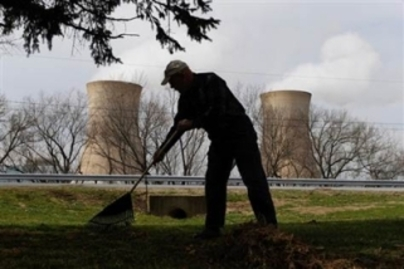 Man rakes leaves with nuclear cooling towers behind