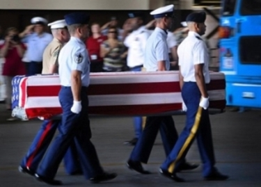Soldiers carry casket draped with flag