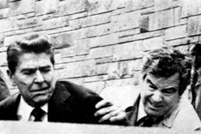 President Reagan being pushed into car by Secret Service agent during assassination attempt