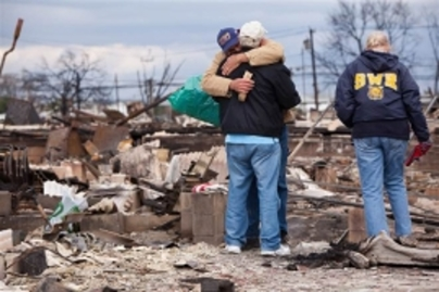 Men hug in the ruins of homes after hurricane