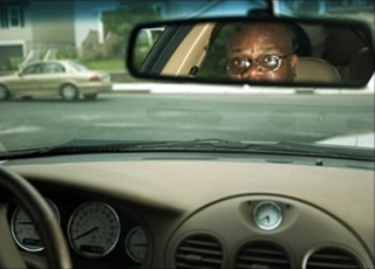 Black man looks in rear-view mirror of car